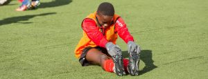 IH Manchester player stretching on pitch