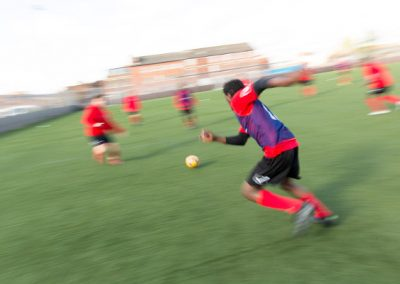 young football player in red kit runs towards the ball in a match