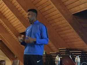 Tall young man in blue tracksuit standing addressing the room