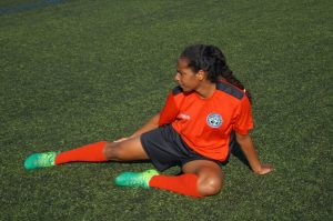 young female player stretches legs after training