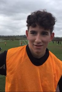 young football player in orange bib talking to camera