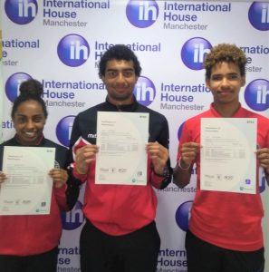3 students; two boys and a girls proudly display their exam certificates in which they all achieved the top grade of Distinction