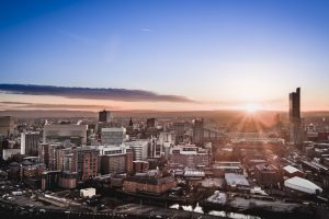 panoramic view of the built up Manchester skyline at dawn with the sun rising.