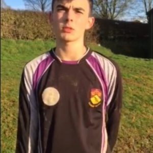 a young football player in his black and purple muddy football shirt looks earnestly into the camera
