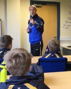 adult male football coach stood at the front of the class, makes a presentation to a group of young players
