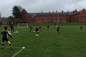 A group of young players training on a grass pitch against a backdrop of a gothic school building and a grey turbulent sky