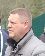 side shot of head and shoulders of senior football coach with short cropped hair