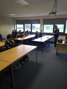 Adult football coach addresses a class of teenage players in matching school kit